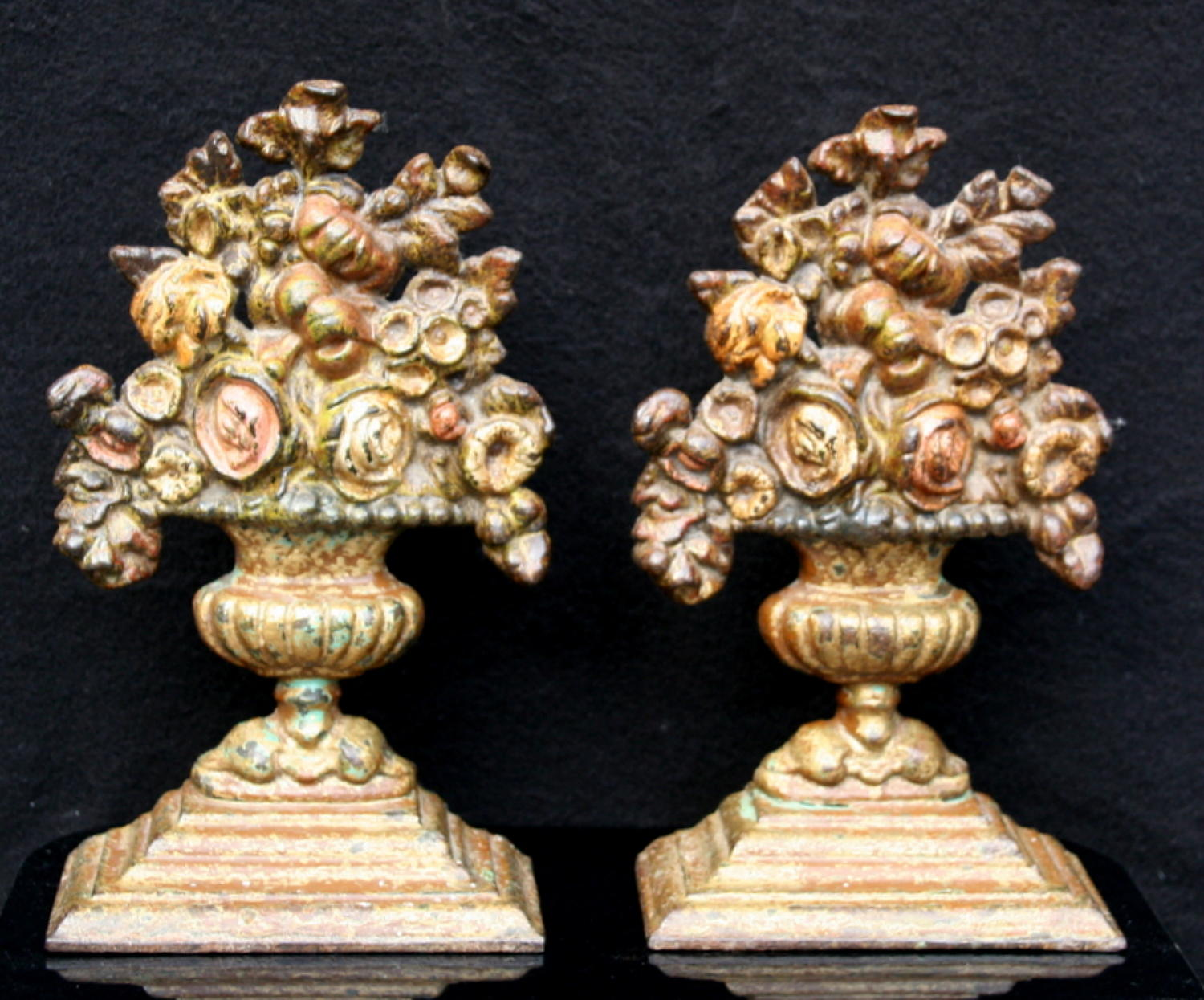 A pair of cast iron chimney ornaments of flowers in urns
